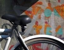 Ποδήλατο που σταθμεύουν ενάντια σε έναν χρωματισμένο γκράφιτι τοίχο Στοκ Φωτογραφίες