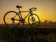 Ποδήλατο στην αγροτική εικόνα τοπίων αχύρου με το πρωί σκιαγραφιών Στοκ Εικόνες