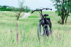 Ποδήλατο στη χλόη και τα λουλούδια λιβαδιών Η έννοια των υπαίθριων δραστηριοτήτων Στοκ εικόνες με δικαίωμα ελεύθερης χρήσης