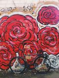 Ποδήλατο των γκρίζος-Μαύρων fixie μπροστά από τον τοίχο με τα φωτεινά κόκκινα γκράφιτι λουλουδιών Στοκ εικόνα με δικαίωμα ελεύθερης χρήσης