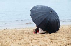 Πολίτης με μια συνεδρίαση ομπρελών στην αμμώδη ακτή στοκ εικόνες