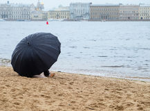 Πολίτης με μια συνεδρίαση ομπρελών στην αμμώδη ακτή στοκ φωτογραφίες