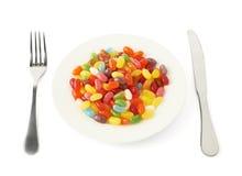 Πολλαπλάσιες ζωηρόχρωμες καραμέλες σε ένα πιάτο που απομονώνεται Στοκ Εικόνες