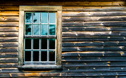 1 πολλαπλάσιο το παράθυρο σε έναν ξεπερασμένο και απανθρακωμένο ξύλινο τοίχο Στοκ Φωτογραφίες