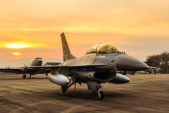 Πολεμικό τζετ γερακιών F-16 στο υπόβαθρο ηλιοβασιλέματος Στοκ Εικόνα