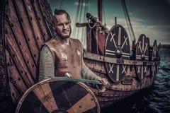 Πολεμιστής Βίκινγκ με το ξίφος και ασπίδα που στέκεται κοντά σε Drakkar στην ακτή Στοκ φωτογραφίες με δικαίωμα ελεύθερης χρήσης