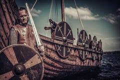 Πολεμιστής Βίκινγκ με το ξίφος και ασπίδα που στέκεται κοντά σε Drakkar στην ακτή Στοκ Εικόνα