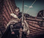 Πολεμιστής Βίκινγκ με το ξίφος που στέκεται κοντά σε Drakkar στην ακτή Στοκ Εικόνα
