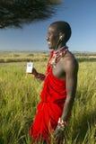Πολεμιστής Masai κοντά στο δέντρο ακακιών που ακούει τη μουσική στο iPod από τη Apple στο κόκκινο τοπίο έρευνας της συντήρησης Le Στοκ εικόνες με δικαίωμα ελεύθερης χρήσης