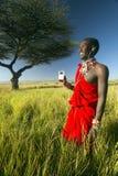 Πολεμιστής Masai κοντά στο δέντρο ακακιών που ακούει τη μουσική στο iPod από τη Apple στο κόκκινο τοπίο έρευνας της συντήρησης Le Στοκ Φωτογραφίες