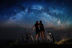 Ποδηλάτες ζεύγους με τα ποδήλατα βουνών τη νύχτα κάτω από τον έναστρο ουρανό Στοκ εικόνα με δικαίωμα ελεύθερης χρήσης