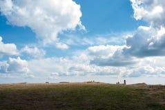 Ποδηλάτες στην απόσταση ενάντια στον ουρανό μεγάλα βουνά βουνών τοπίων Η σκιά στο έδαφος Εντυπωσιακοί ουρανοί Στοκ φωτογραφία με δικαίωμα ελεύθερης χρήσης