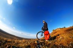 Ποδηλάτης βουνών που εξετάζει την άποψη και που ταξιδεύει στο ποδήλατο με το σακίδιο πλάτης Στοκ Εικόνες