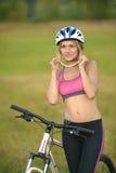 Ποδηλάτης γυναικών στα πλαίσια της πράσινης χλόης Στοκ φωτογραφία με δικαίωμα ελεύθερης χρήσης