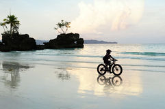 Ποδηλάτης και η αντανάκλασή της στην παραλία Boracay Στοκ Φωτογραφίες