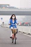 Ποδηλάτης καλμένη στην αιθαλομίχλη πόλη, Πεκίνο, Κίνα Στοκ Εικόνες