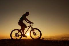 Ποδηλάτης-κορίτσι στο ηλιοβασίλεμα Στοκ φωτογραφίες με δικαίωμα ελεύθερης χρήσης