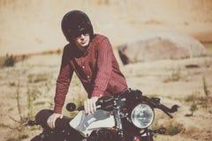 Ποδηλάτης με την έναρξη κρανών μια εκλεκτής ποιότητας μοτοσικλέτα συνήθειας Υπαίθριο τονισμένο τρόπος ζωής πορτρέτο Στοκ Φωτογραφία
