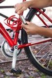 Ποδηλάτης που εξασφαλίζει το ποδήλατο με την κλειδαριά Στοκ Φωτογραφία