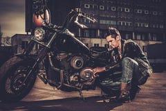 Ποδηλάτης που επισκευάζει τη μοτοσικλέτα συνήθειάς του bobber στοκ εικόνα