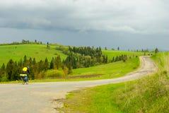 Ποδηλάτης που οδηγά στο δρόμο πράσινοι λόφοι Δρόμος με πολλ'ες στροφές Ένας ποδηλάτης οδηγά στο στόχο Στοκ Φωτογραφία