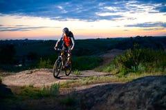 Ποδηλάτης που οδηγά το ποδήλατο στο δύσκολο ίχνος βουνών στο ηλιοβασίλεμα Στοκ Εικόνες