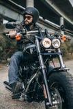 Ποδηλάτης στη συνεδρίαση σακακιών κρανών και δέρματος σε μια μοτοσικλέτα Στοκ φωτογραφίες με δικαίωμα ελεύθερης χρήσης