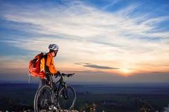 ποδηλάτης στο υπόβαθρο βουνό-ποδηλάτων του όμορφου ηλιοβασιλέματος Στοκ Φωτογραφία