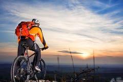 ποδηλάτης στο υπόβαθρο βουνό-ποδηλάτων του όμορφου ηλιοβασιλέματος Στοκ Εικόνα