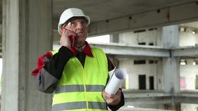 Πολιτικός μηχανικός με το τηλέφωνο κυττάρων στο εργοτάξιο οικοδομής απόθεμα βίντεο