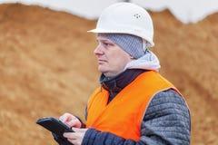 Πολιτικός μηχανικός με το PC ταμπλετών σε έναν σωρό της άμμου Στοκ Εικόνες