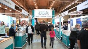 Πολλοί άνθρωποι στο περίπτερο επισκέπτονται την Αμερική στη μεγάλη Διεθνή Έκθεση των ταξιδιωτικών γραφείων απόθεμα βίντεο