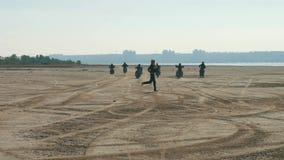 Πολλοί μοτοσυκλετιστές που οδηγούν κατά μήκος της αμμώδους παραλίας μακριά Οι ποδηλάτες σέρνουν τη φυλή με το κορίτσι απόθεμα βίντεο