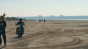 Πολλοί μοτοσυκλετιστές που συναγωνίζονται το κορίτσι αναζήτησης κατά μήκος της αμμώδους παραλίας από μακριά απόθεμα βίντεο