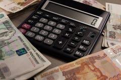 Πολλοί ρωσικοί χρήματα και υπολογιστής σε ένα ξύλινο υπόβαθρο Στοκ Εικόνες