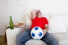 Ποδοσφαιρικό παιχνίδι προσοχής ανεμιστήρων ποδοσφαίρου στη λυπημένη απογοητευμένη κλίση TV στον καναπέ μάταιο Στοκ Εικόνες