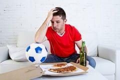 Ποδοσφαιρικό παιχνίδι προσοχής ανεμιστήρων ποδοσφαίρου λυπημένη απογοητευμένη TV και απελπισμένος Στοκ Εικόνα