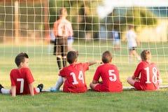 Ποδοσφαιριστές παιδιών που κάθονται πίσω από τον αγώνα ποδοσφαίρου προσοχής στόχου Στοκ εικόνες με δικαίωμα ελεύθερης χρήσης