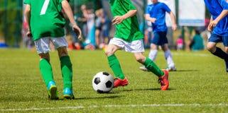 Ποδοσφαιριστές παιδιών που τρέχουν με τη σφαίρα Παιδιά στο μπλε και Στοκ Εικόνες