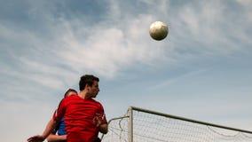 Ποδοσφαιριστές που πηδούν επάνω και που αντιμετωπίζουν για τη σφαίρα απόθεμα βίντεο