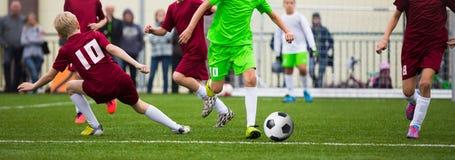 Ποδοσφαιριστές ποδοσφαίρου παιδιών Ποδοσφαιριστές που κλωτσούν το παιχνίδι αγώνων ποδοσφαίρου στη χλόη Στοκ φωτογραφία με δικαίωμα ελεύθερης χρήσης