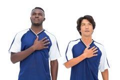 Ποδοσφαιριστές στο μπλε άκουσμα τον ύμνο Στοκ φωτογραφία με δικαίωμα ελεύθερης χρήσης
