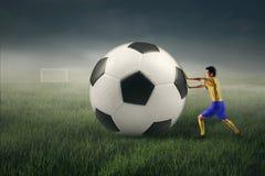 Ποδοσφαιριστής με μια μεγάλη σφαίρα Στοκ Εικόνα