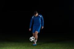 Ποδοσφαιριστής με μια σφαίρα στο μαύρο υπόβαθρο Στοκ φωτογραφία με δικαίωμα ελεύθερης χρήσης