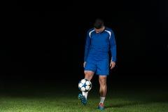 Ποδοσφαιριστής με μια σφαίρα στο μαύρο υπόβαθρο Στοκ Φωτογραφίες