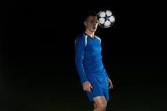 Ποδοσφαιριστής με μια σφαίρα στο μαύρο υπόβαθρο Στοκ φωτογραφίες με δικαίωμα ελεύθερης χρήσης