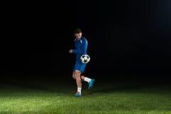 Ποδοσφαιριστής με μια σφαίρα στο μαύρο υπόβαθρο Στοκ εικόνες με δικαίωμα ελεύθερης χρήσης