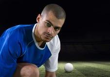 ποδοσφαιριστής που δένει τις δαντέλλες στον τομέα με μια σφαίρα πίσω από τον Στοκ Φωτογραφίες