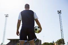 Ποδοσφαιριστής που στέκεται με μια σφαίρα Στοκ Εικόνες