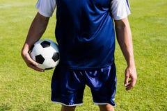 Ποδοσφαιριστής που στέκεται με μια σφαίρα Στοκ εικόνες με δικαίωμα ελεύθερης χρήσης